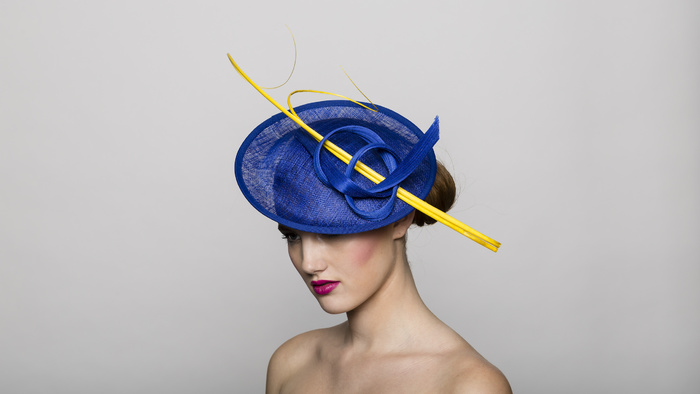 Hand-blocked blue sinamay disc hat base with buntal straw and yellow feather trims.
