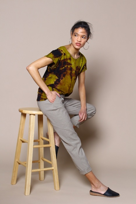 Model sitting on stool with green tie dye shirt and grey pants